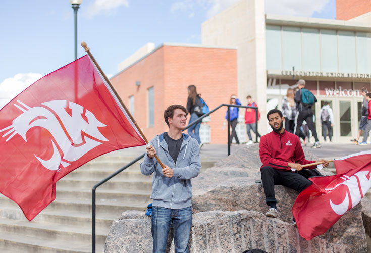 Two students outside of the CUB waving WSU flags